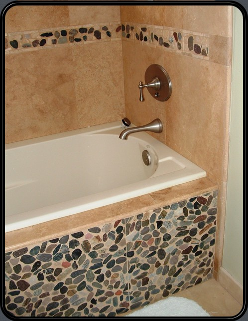 Travertine with river rock accents, notice the access panel for tub